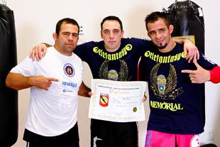 Amaury Bitetti and Marcelo Nigue presenting Gene Simco with his Black Belt Certificate